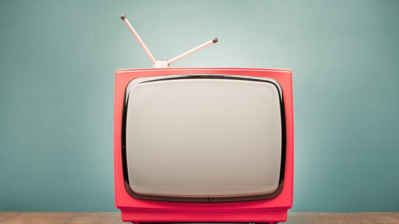téléviseur rétro rouge avec une antenne devant un mur menthe